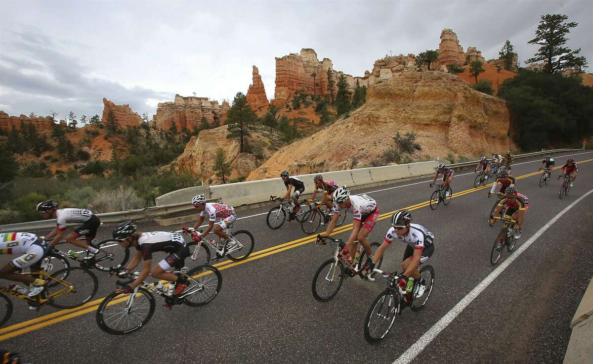 FILE - In this Aug. 7, 2013, file photo, riders race through a section of Bryce Canyon National Park during the second stage of the Tour of Utah cycling race from Panguitch to Torrey, Utah. Motorized electric bicycles may soon be humming their way into serene national parks and other public lands nationwide, under a new Trump administration order hotly opposed by many outdoors groups allowing the so-called e-bikes on every federal trail where a regular bike can go. (Francisco Kjolseth/The Salt Lake Tribune via AP, File)