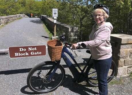 FILE-In this June 8, 2019 file photo, Janice Goodwin stands by her electric-assist bicycle at a gate near the start of the carriage path system where bikes such as her are banned inside Acadia National Park, in this photo June 8, 2018, in Bar Harbor, Maine. Interior Secretary David Bernhardt signed the order on Thursday allowing motorized electric bicycles into national parks and other public lands.