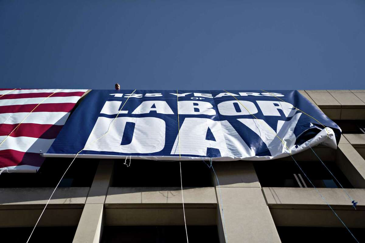 A Labor Day banner is unfurled outside the U.S. Department of Labor headquarters in Washington. The issue of how many jobs Americans have at one time is a personal decision that we make for ourselves, as we try to balance our financial obligations with our familial commitments.
