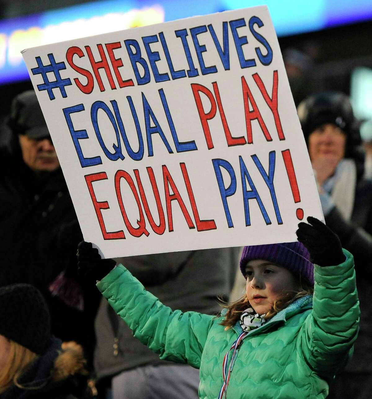 A girl holds up a sign for equal pay for the U.S. women soccer players, during the first half of a 2016 international friendly soccer match between the United States and Colombia, in East Hartford, Conn.