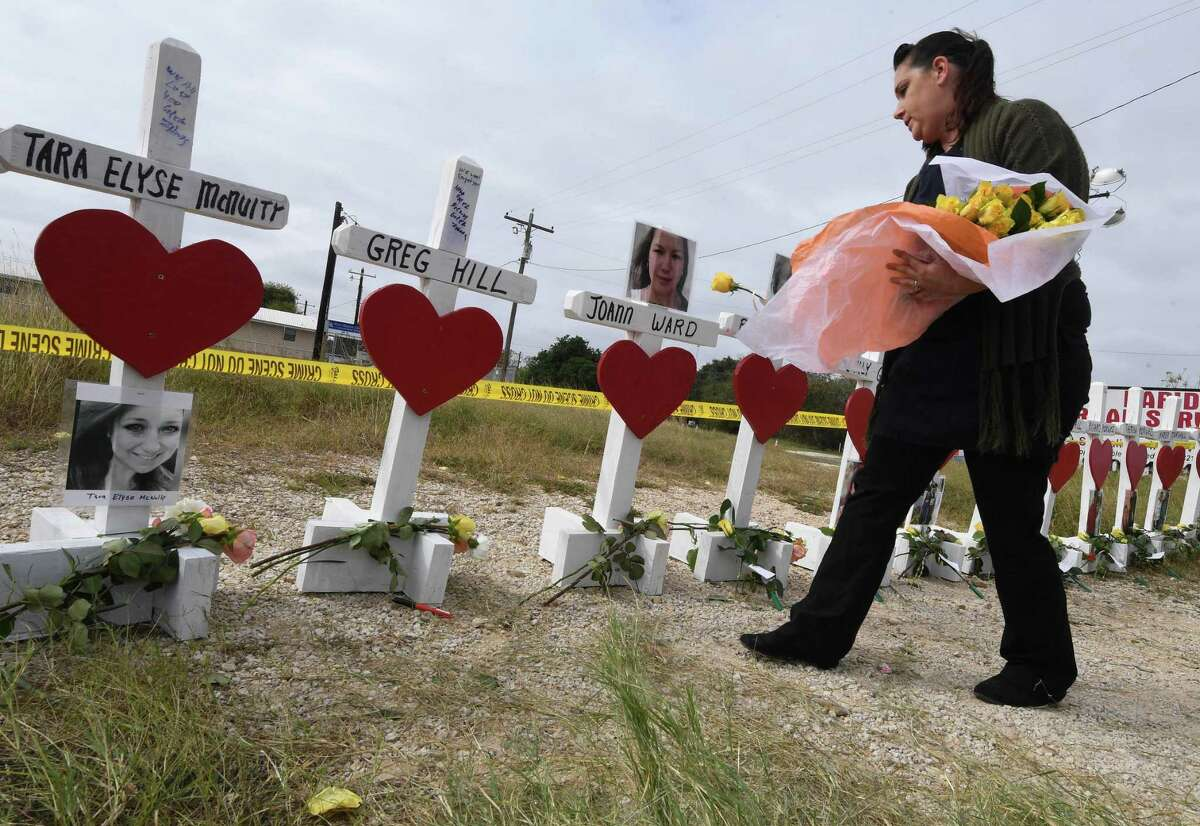 Jessica Mires leaves flowers on crosses named for the victims outside the First Baptist Church, which was the scene of the mass shooting that killed 26 people in Sutherland Springs, Texas on November 9, 2017. Willeford shot suspect Devin Patrick Kelley, a gunman wearing all black armed with an assault rifle that opened fire on a small-town Texas church during Sunday morning services, on November 5, killing 26 people and wounding 20 more in the last mass shooting to shock the United States. / AFP PHOTO / MARK RALSTONMARK RALSTON/AFP/Getty Images