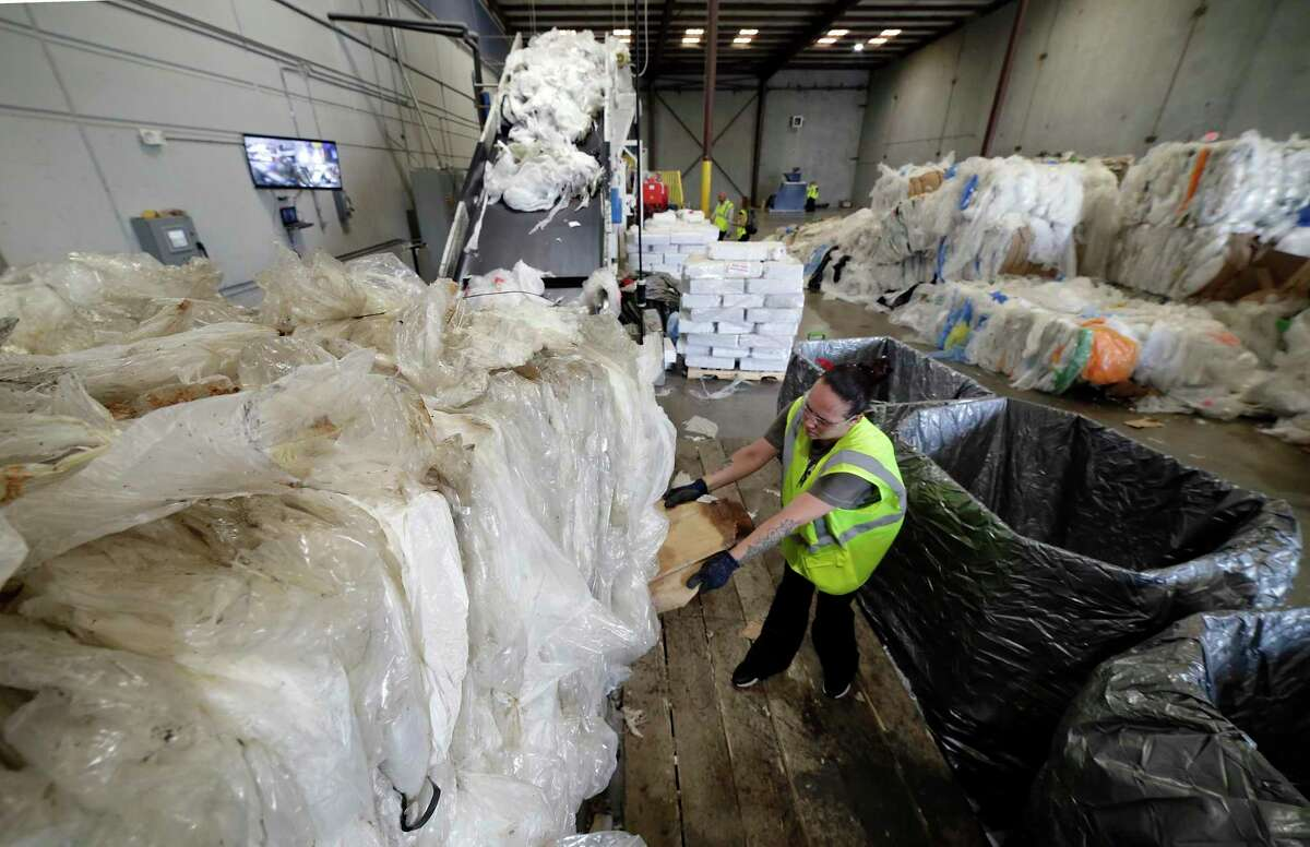 Miranda Leal breaks open a bale of used plastic film at the Avangard Innovative recycling facility and company headquarters Wednesday, Aug. 28, 2019 in Houston, TX.