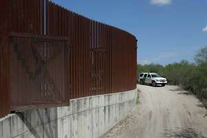 FILE - In this Aug. 11, 2017, file photo, a U.S. Customs and Border Patrol vehicle passes along a section of border levee wall in Hidalgo, Texas. The U.S. government is preparing to begin construction of more border walls and fencing in South Texas' Rio Grande Valley, likely on federally-owned land set aside as wildlife refuge property. Heavy construction equipment is supposed to arrive starting Monday. A photo posted by the nonprofit National Butterfly Center shows an excavator parked on its property. (AP Photo/Eric Gay, File)