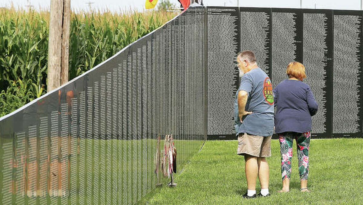 Dan Dona of Roxana stares at the names of U.S. miltary personnel who died during the Vietnam War listed on the American Veterans Traveling Tribute wall now set up behind Parkside Primary School in Bethalto. The wall, and a static military display, are located behind the school as part of the 100th anniversary of the Bethalto Homecoming. The wall is free to the public and open 24 hours a day through Labor Day. The homecoming also runs through Labor Day. Additional photos will be in Sunday's edition of The Telegraph and online at www.thetelegraph.com.