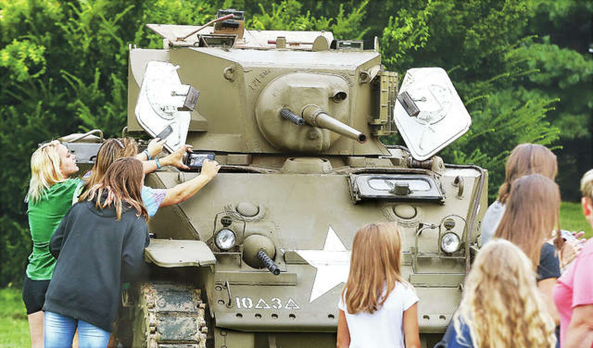 Three young women work to get a picture inside the Stuart M3 light tank set up as part of the static military display. The World War II tank was brought to the school grounds by Stutz Excavating, courtesy of owner Keith Moore of Webster Groves, Missouri.