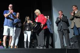 Maureen Kersten of Dickinson is given a Rascal Flatts autographed guitar in recognition of being the one millionth fan at the Smart Financial Centre on Thursday, Aug. 29.
