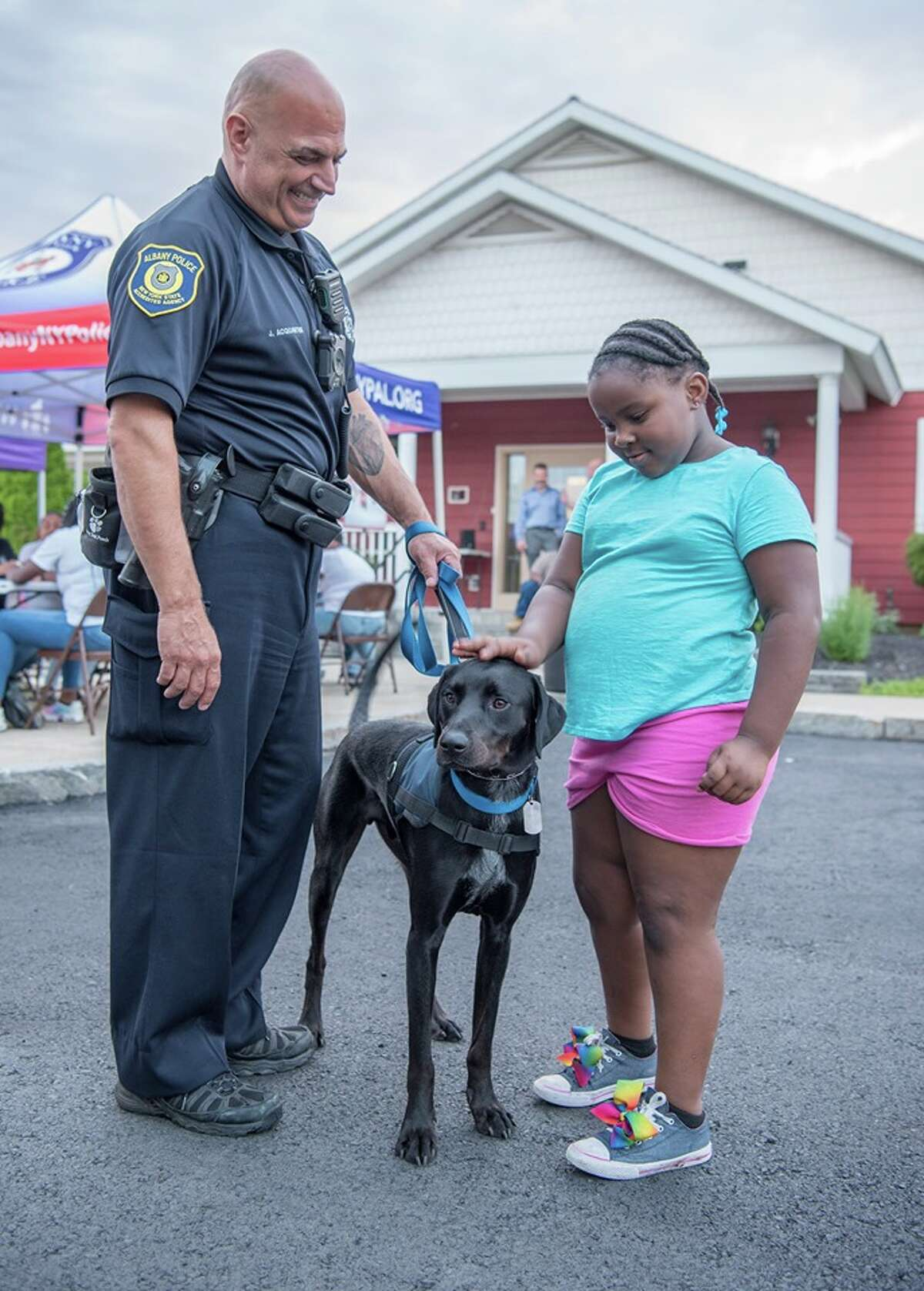 Albany police Officer Joseph Lynch and Albany police therapy dog Finn interact with a child in this undated photo.