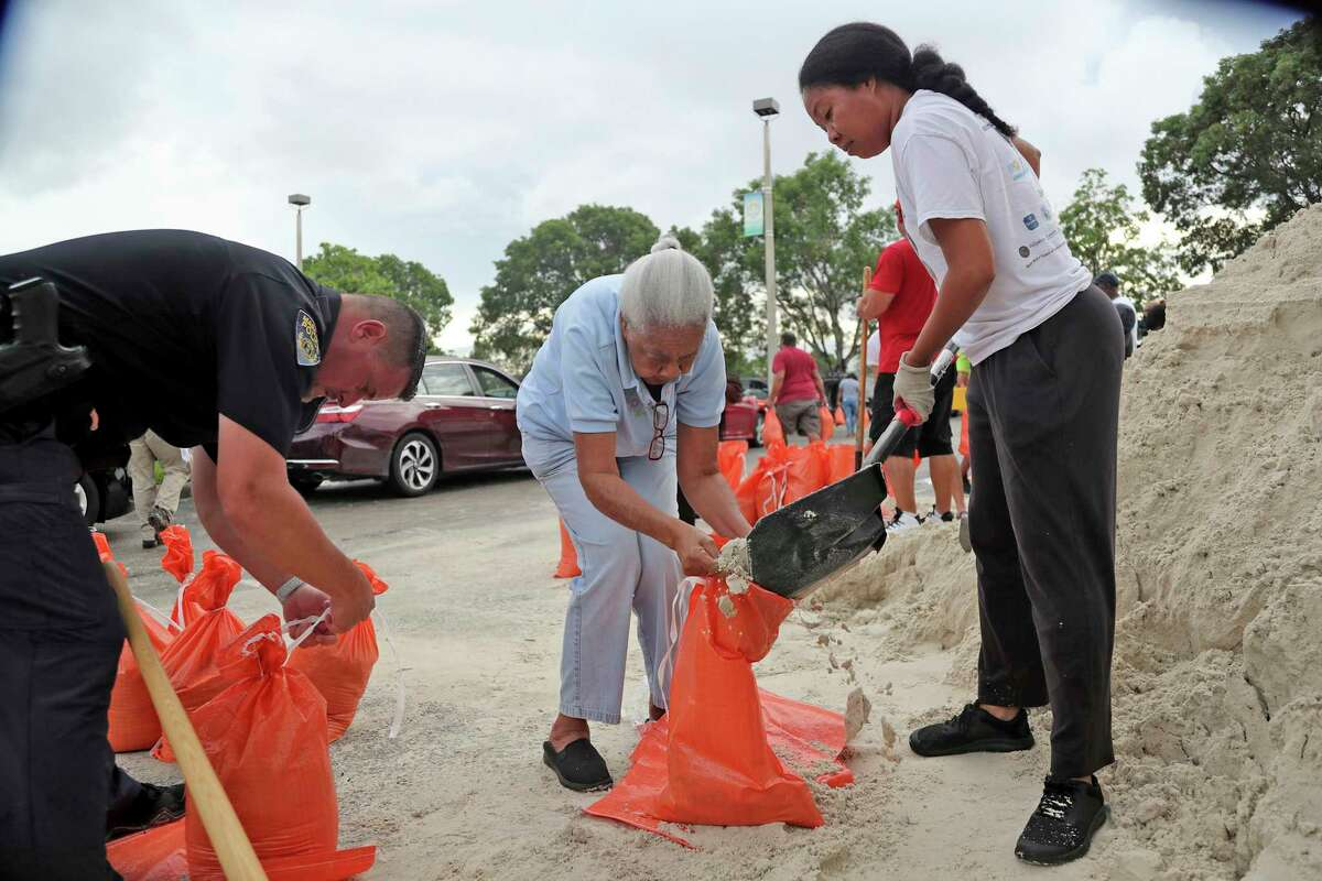 Joan Chang, center, gets help filling her bags during a sandbag giveaway in preparation for Hurricane Dorian, Friday, Aug. 30, 2019, in Margate, Fla. (Amy Beth Bennett/South Florida Sun-Sentinel via AP)