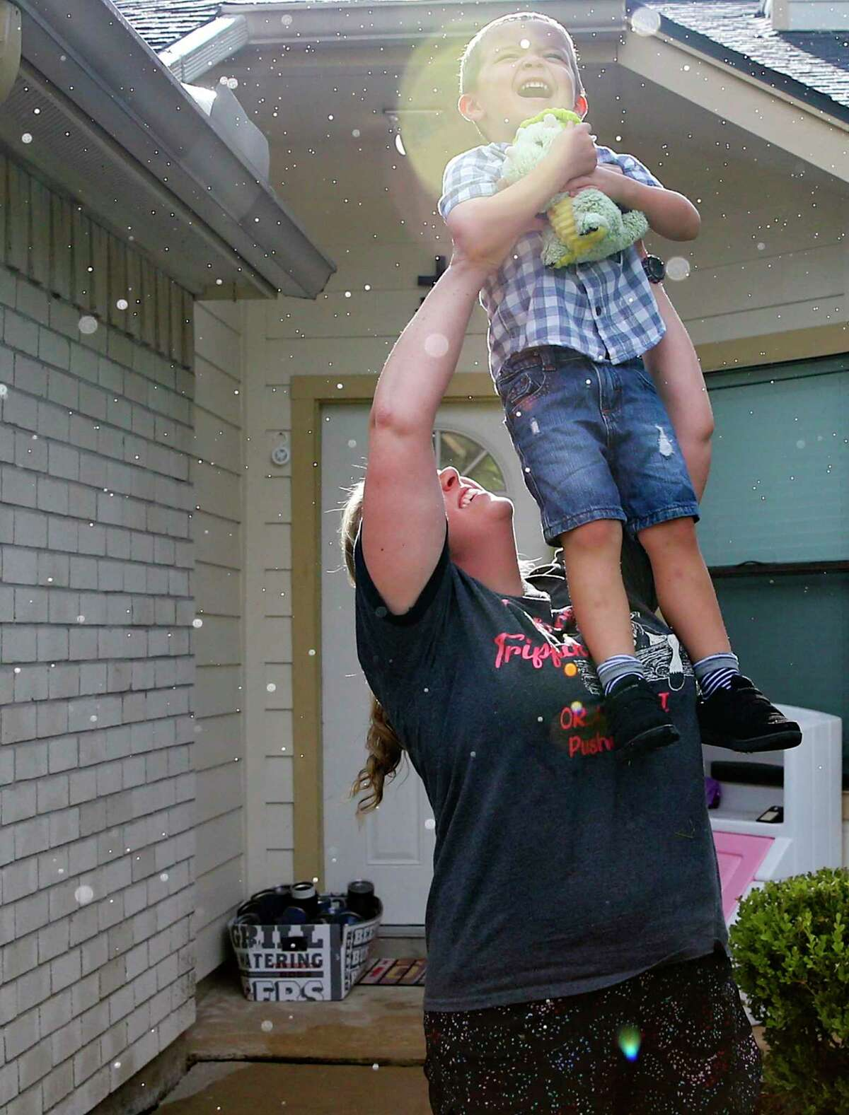 Janet Clements lifts up her son, Jackson, 4, so he can get a better look at a rainbow in front of their Katy, Texas, home on Friday, Aug. 30, 2019 in Katy. The family was flooded out of their last home from Harvey.
