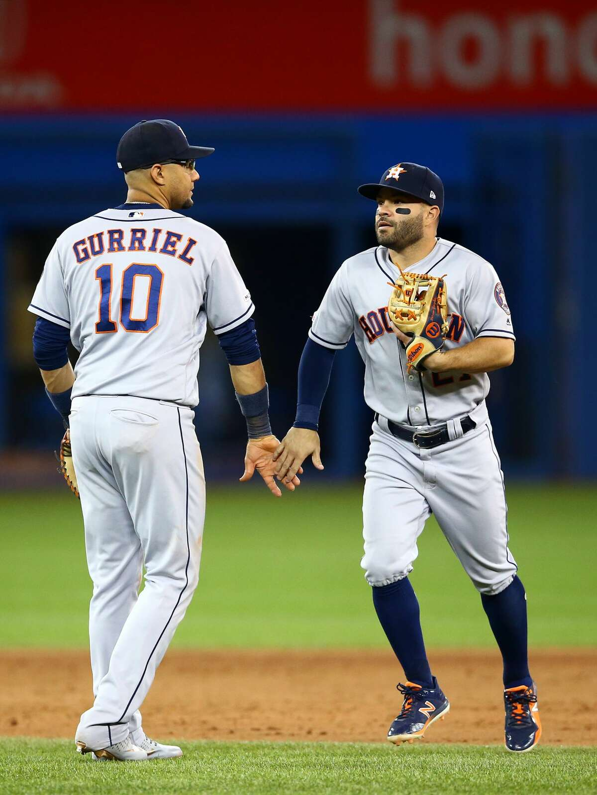 TORONTO, ON - AUGUST 30: Yuli Gurriel #10 and Jose Altuve #27 of the Houston Astros celebrate following victory during a MLB game against the Toronto Blue Jays at Rogers Centre on August 30, 2019 in Toronto, Canada. (Photo by Vaughn Ridley/Getty Images)