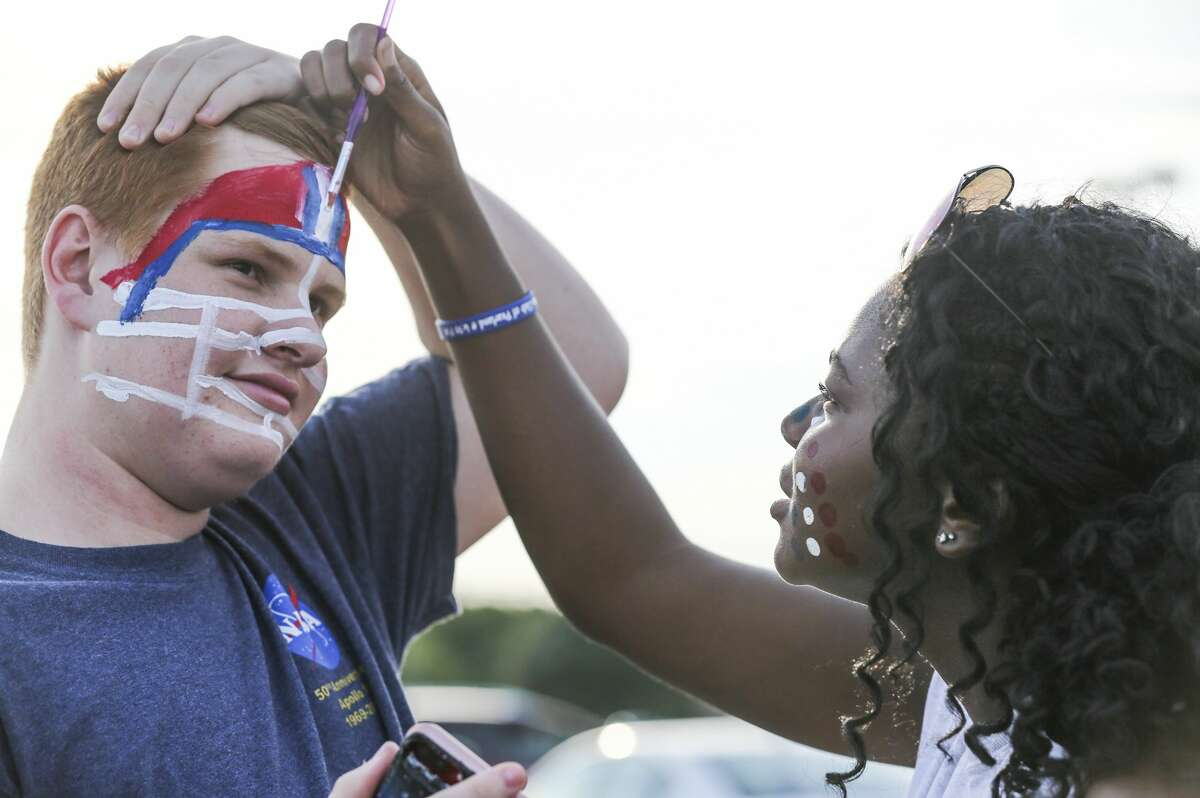 USA: TX: Pearland: Dawson Sophomore Stuart Byrne has his face painted by Dawson Junior Gabrielle Lewis before the Dawson Eagles played the Oak Ridge War Eagles on August 30, 2019 at The Rig in Pearland, TX.