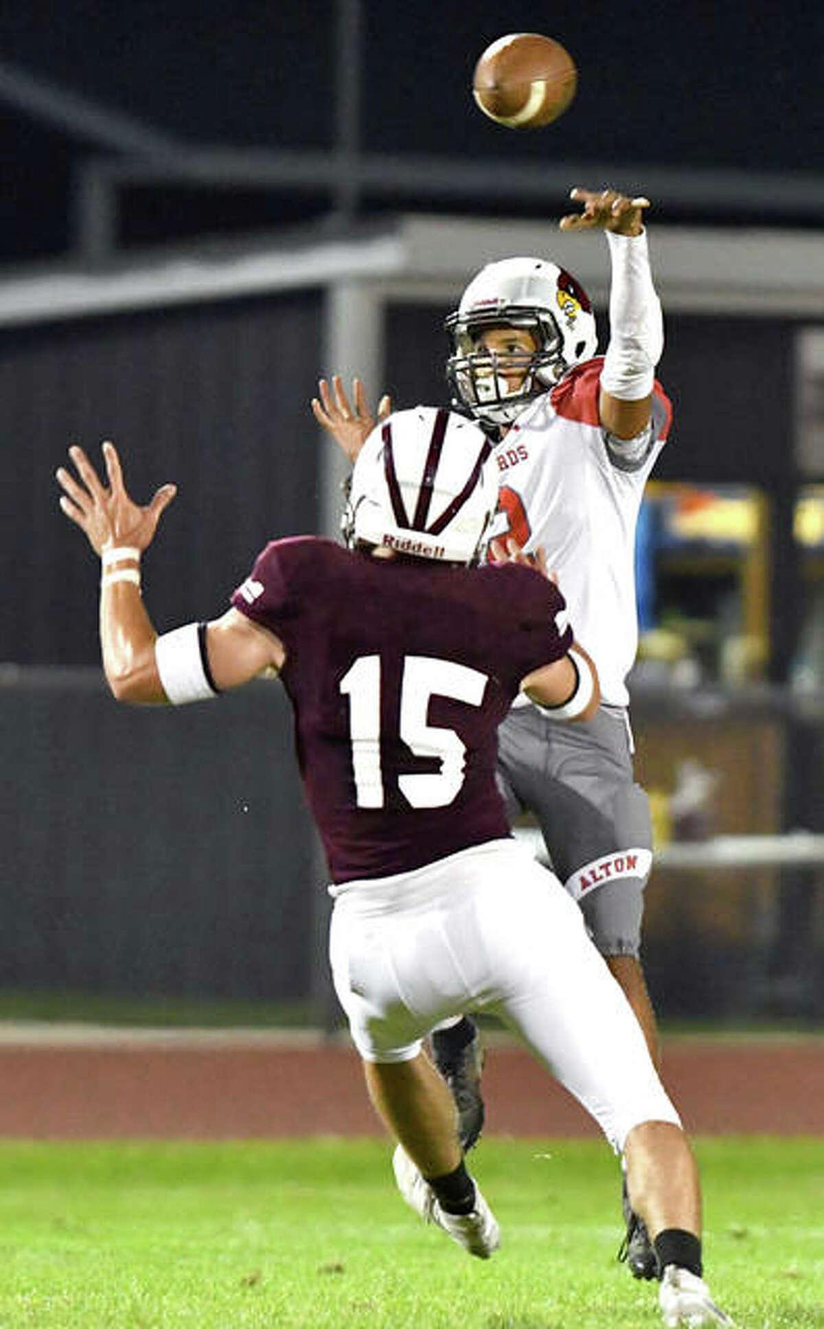 Alton quarterback Andrew Jones passes the ball over Moline's Immanuel Bailey in the second quarter Friday night in Moline.