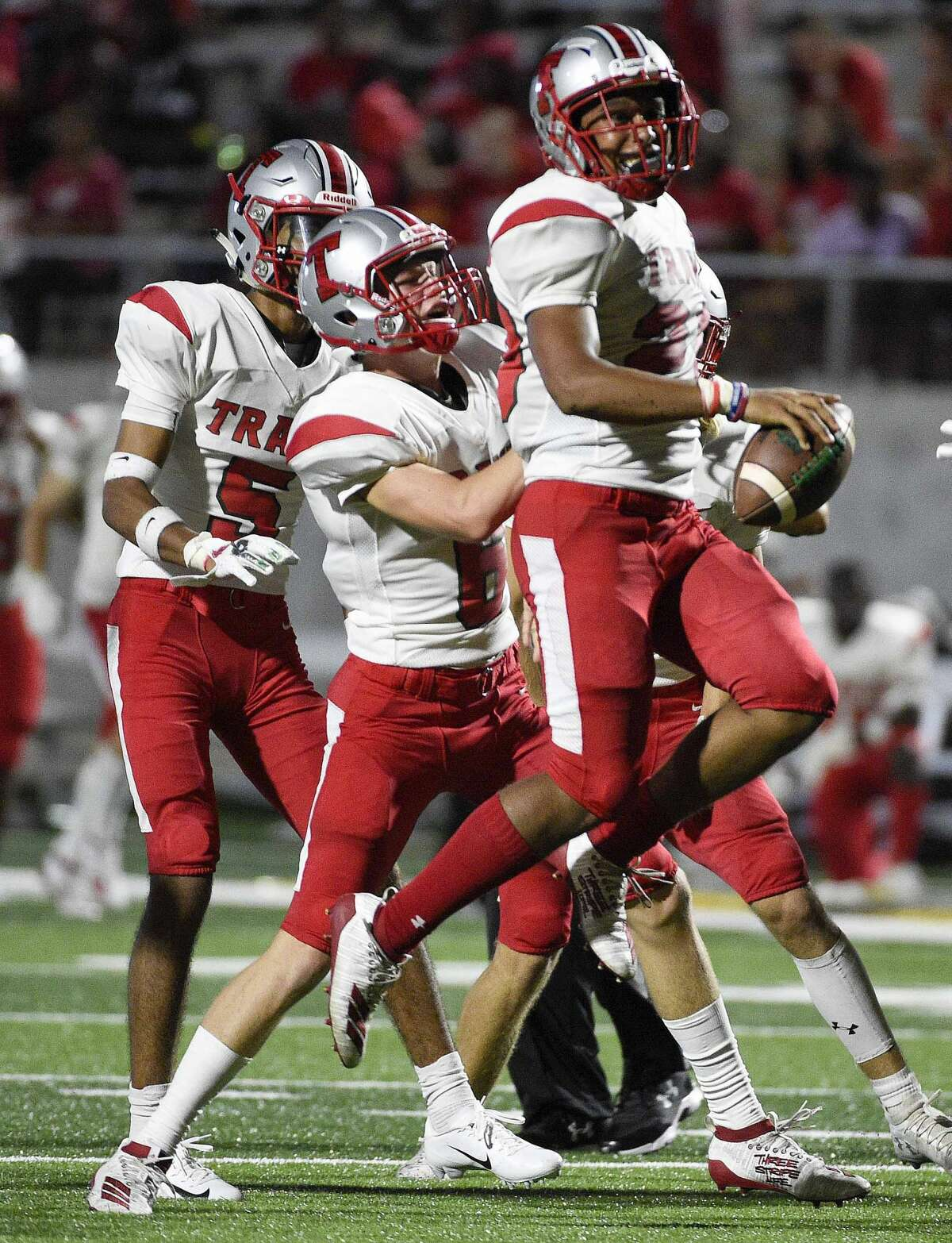 Travis linebacker Marcus Trevino, right, celebrates his fumble recovery with defensive back Mason Muchaw during the second half of a high school football game against Hightower, Friday, Aug. 30, 2019, in Iowa Colony, TX.