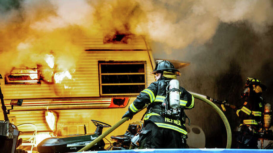 Alton firefighters attempt to knock down flames that overtook a camper in the 900 block of Hampton Friday. Photo: Nathan Woodside | The Telegraph