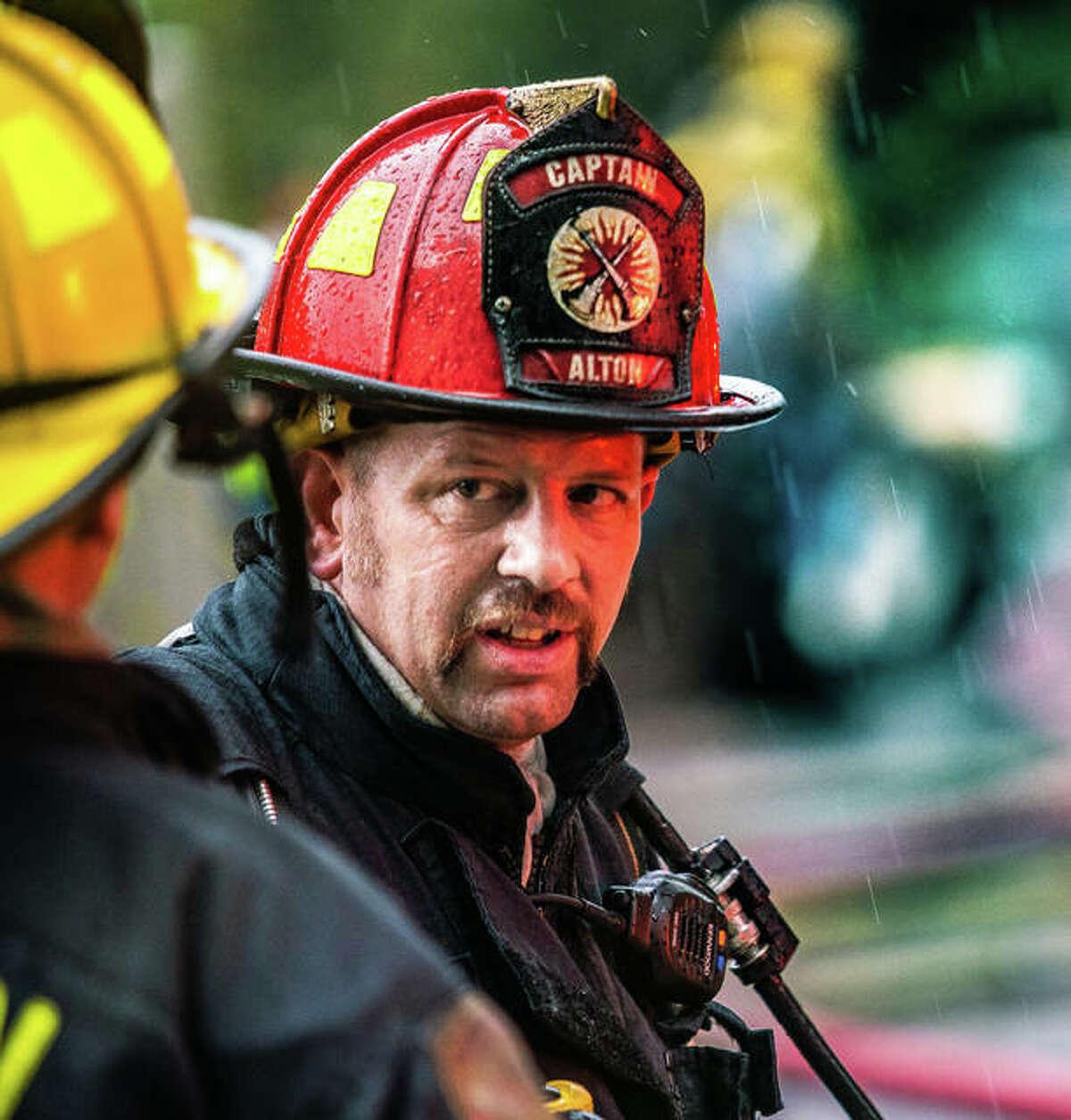 Alton Fire Captain Dan Whiteside speaks with a colleague as a heavy rain falls Friday during a fire call on Hampton Street in Alton.
