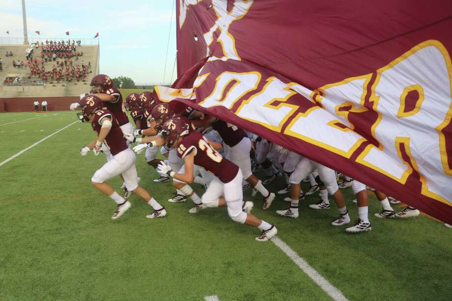 Deer Park's players run through its banner to officially get the 2019 season under way Friday night. Photo: Robert Avery