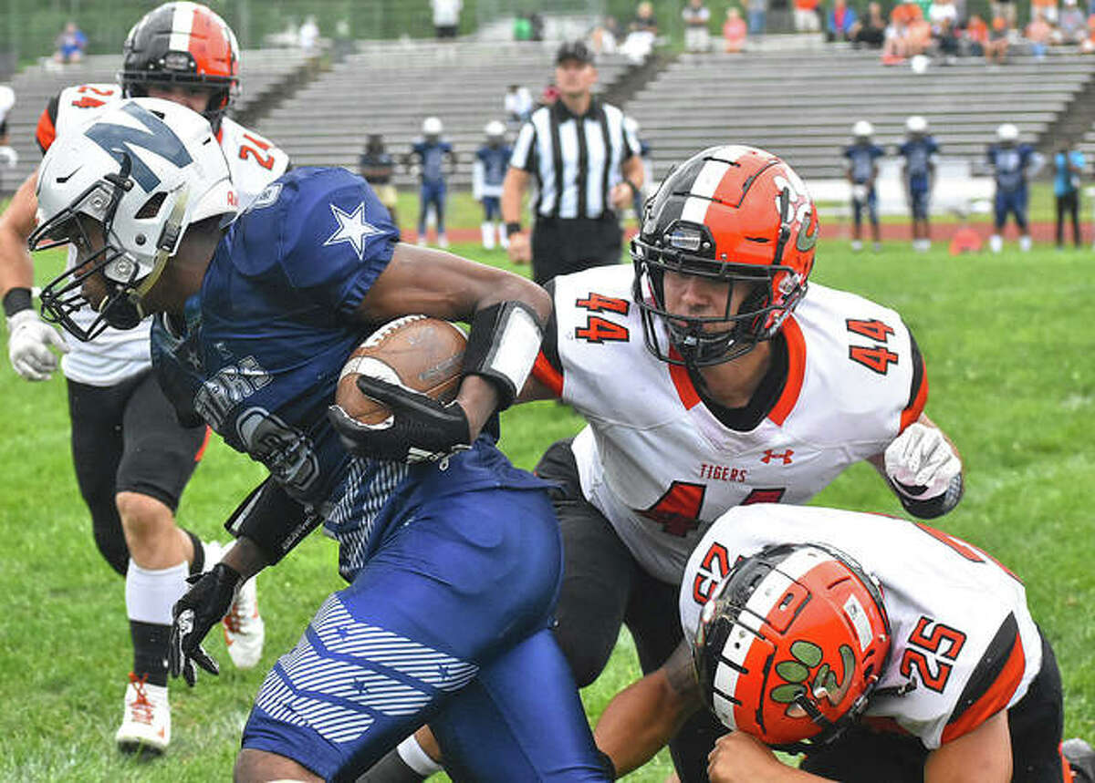 Edwardsville linebackers Evan Ramirez (44) and Eric Epenesa (25) try to take down the McCluer North ballcarrier in the first quarter in Florissant, Missouri.