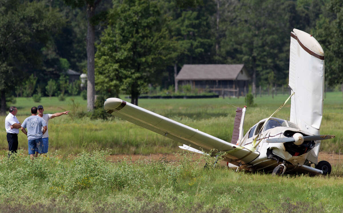 A plan is moved from a small pond after it crashed, injuring two people with minor injuries along Seven Coves Road near Farrell Road, Saturday, Aug. 31, 2019, in Willis. The plane was headed for Conroe-North Houston Regional Airport when air traffic controllers dispatched firefighters for a report of an aircraft emergency.