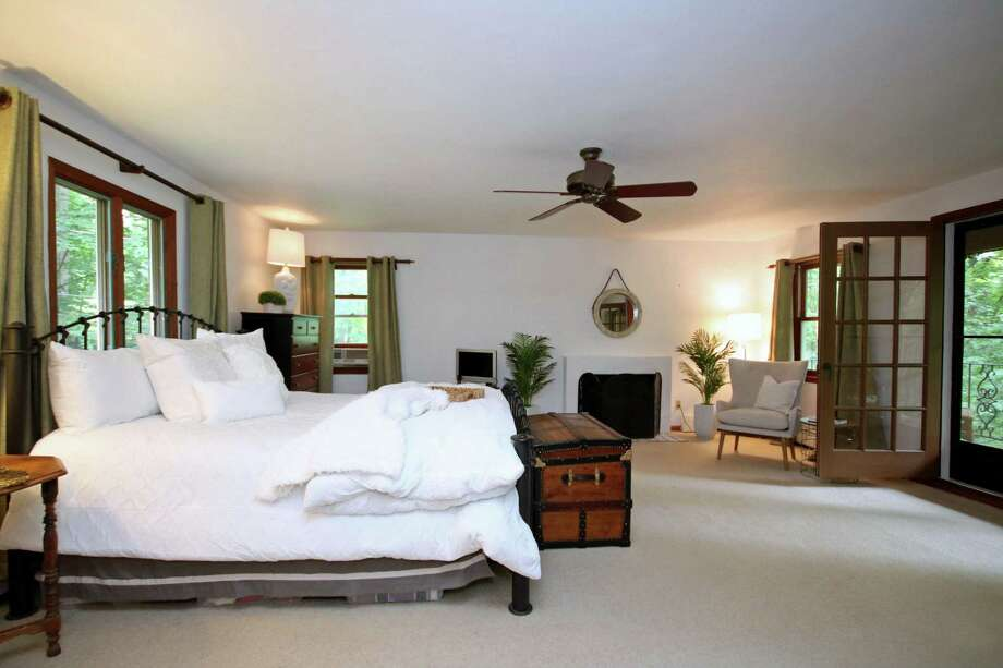 The spacious master suite features a fireplace, ceiling fan, French doors to a large private deck, and a full bath. Photo: Picasa