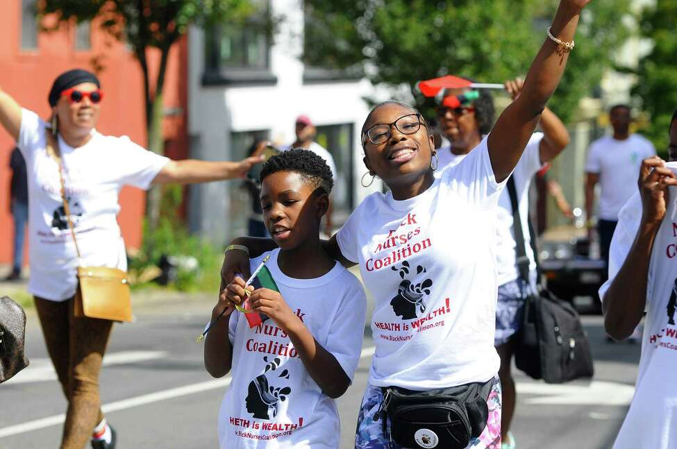 Jah-Raii Gause puts an arm around her nephew, U-Rain Gause as she leads a chant for the Black Nurses Coalition during the Capital Region's first African Heritage Parade in Albany, N.Y. on Saturday, Aug. 31, 2019. (Jenn March, Special to the Times Union )