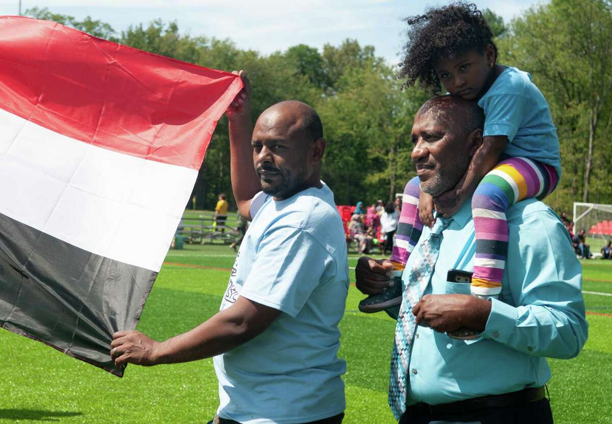Sudanese Soccer Tournament organizer Yasir Nasir, right, holds his 3-year-old daughter, Ghazal during the tournament's welcome ceremony at Afrim's Sports Park in Colonie, N.Y. on Saturday, Aug. 31, 2019. (Jenn March, Special to the Times Union )
