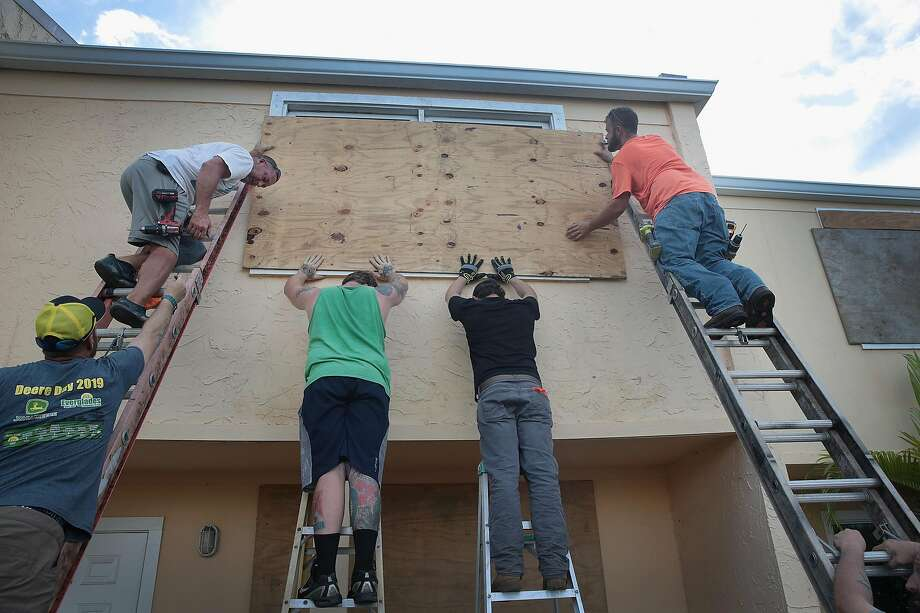 Residents of Fort Pierce, Fla., board up an apartment building to protect it from Hurricane Dorian. The storm is now expected to turn north and remain off the Florida coast. Photo: Scott Olson / Getty Images