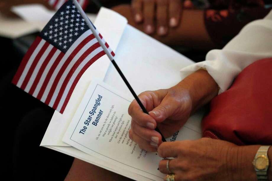 ARCHIVO — En esta fotografía de archivo del 16 de agosto de 2019, una aspirante a ser ciudadana de Estados Unidos sostiene una bandera del país y la letra del himno nacional antes de una ceremonia de naturalización en una oficina del Servicio de Ciudadanía e Inmigración en Miami. Photo: Wilfredo Lee /Associated Press / Copyright 2019 The Associated Press. All rights reserved