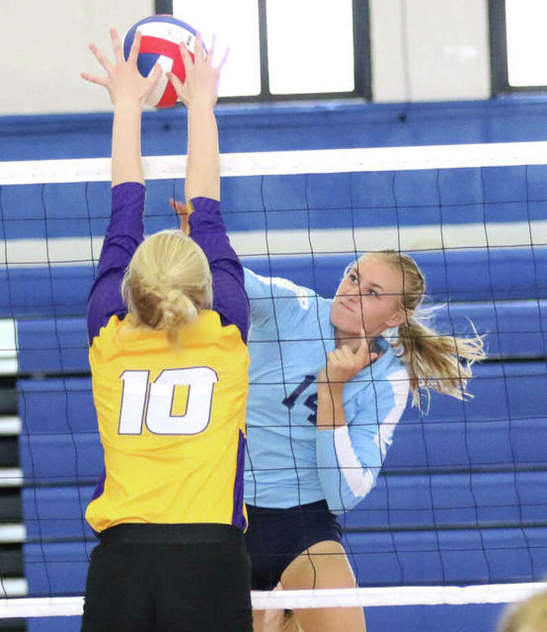 Jersey's Lauren Brown (right) hits into the block of CM's Claire Christeson during the championship match of the Roxana Tournament on Saturday at Milazzo Gym. Photo: Greg Shashack / The Telegraph