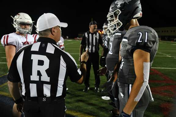 Tomball senior quarterback Hunter Dunn, left, and Tomball Memorial senior wide receiver Logan Kyle (21) get their instructions from the game referee during the coin toss before their non-district football season opener at Tomball Stadium on August 30, 2019.