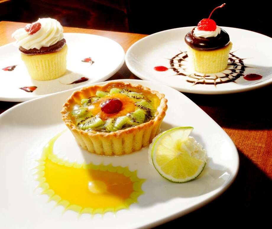A house-made fruit tart and cupcakes from Coccadotts Cake Shop in Colonie share menu space at the new Central Steak. (Luanne M. Ferris / Times Union) Photo: LUANNE M. FERRIS