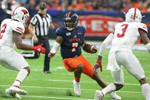 Roadrunner quarterback Frank Harris scrambles away from tacklers as UTSA plays UIW at the Alamodome on August 31, 2019.