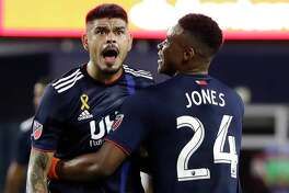 New England Revolution's Gustavo Bou, left, celebrates his goal with teammate DeJuan Jones (24) in the second half of an MLS soccer match against Toronto FC at Gillette Stadium, Saturday, Aug. 31, 2019, in Foxborough, Mass. The match ended in a 1-1 tie. (AP Photo/Elise Amendola)