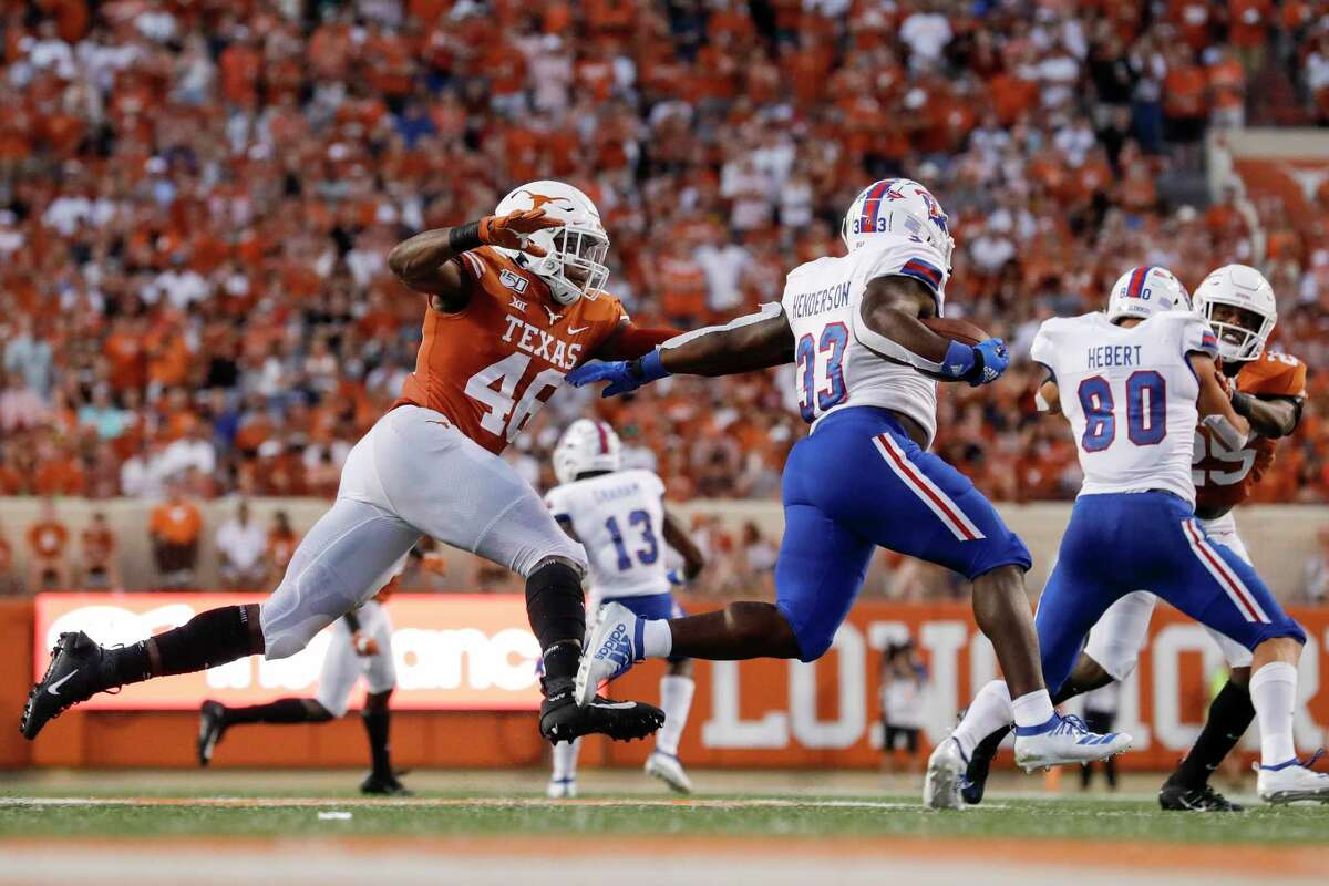 AUSTIN, TX - AUGUST 31: Justin Henderson #33 of the Louisiana Tech Bulldogs runs the ball pursued by Joseph Ossai #46 of the Texas Longhorns in the second quarter at Darrell K Royal-Texas Memorial Stadium on August 31, 2019 in Austin, Texas.