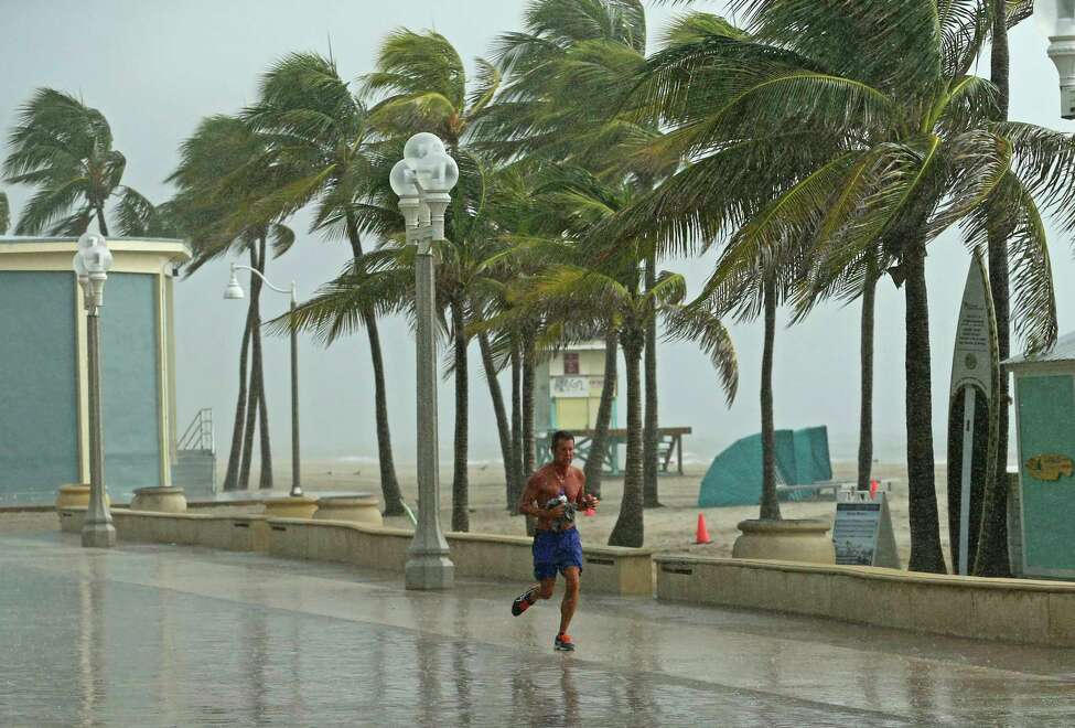 A beachgoer runs under the rain at the Hollywood Beach Broadwalk on Saturday, Aug. 31, 2019 Hollywood, Fla. The latest forecast says Hurricane Dorian is expected to stay just off shore of Florida and skirt the coast of Georgia, with the possibility of landfall still a threat on Wednesday, and then continuing up to South Carolina early Thursday. (David Santiago/Miami Herald via AP)