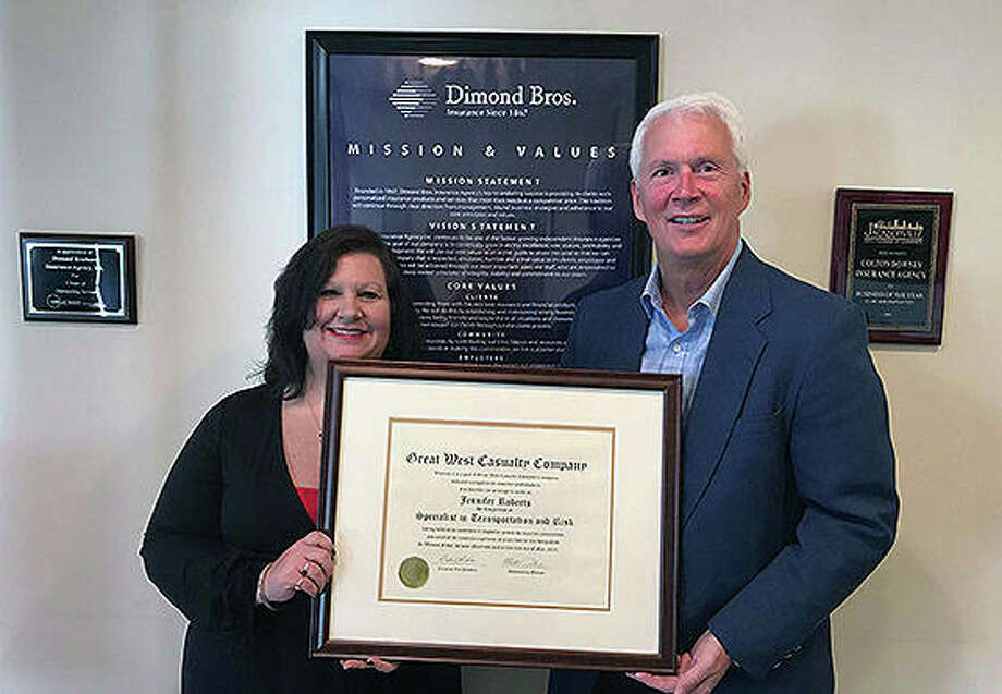 Jennifer Roberts (left), account executive for Dimond Bros. Insurance, receives a plaque commemorating earning the specialist in transportation and risk designation from Dan Martin, senior marketing representative for Great West Casualty Co. Photo: Photo Provided