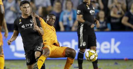 Sporting Kansas City midfielder Felipe Gutierrez (21) and Houston Dynamo midfielder Oscar Garcia collide while chasing the ball during the first half of an MLS soccer match Saturday, Aug. 31, 2019, in Kansas City, Kan. (AP Photo/Charlie Riedel)