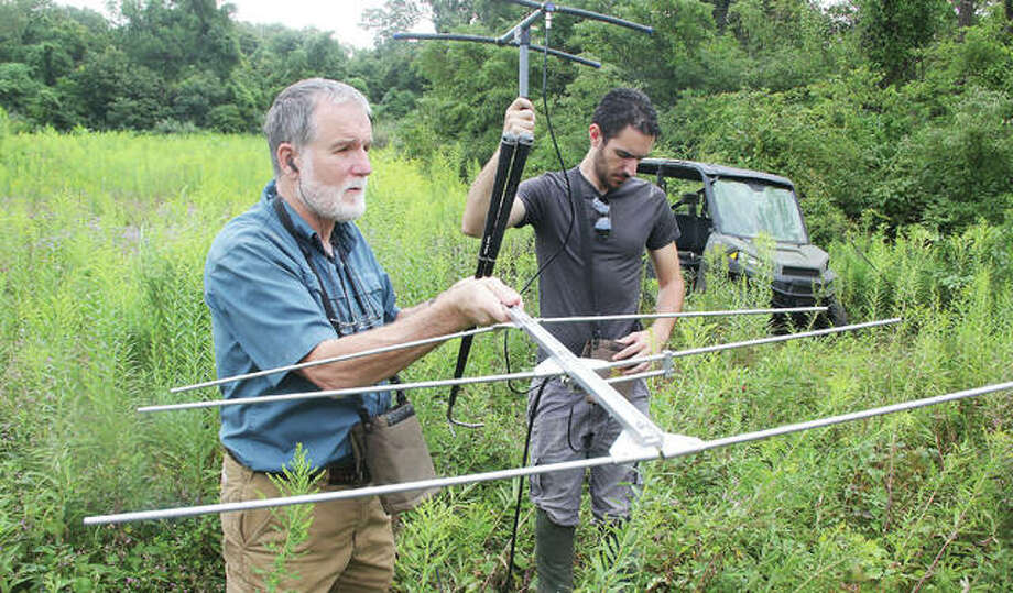 Dr. Scott Eckert, left, chair of the Biology Department at Principia College, and staff biologist Ian Armesy, use radio receivers to look for a timber rattlesnake on college property. Eckert has been studying the snake's movement for about five years, and they are currently monitoring about a dozen snakes.