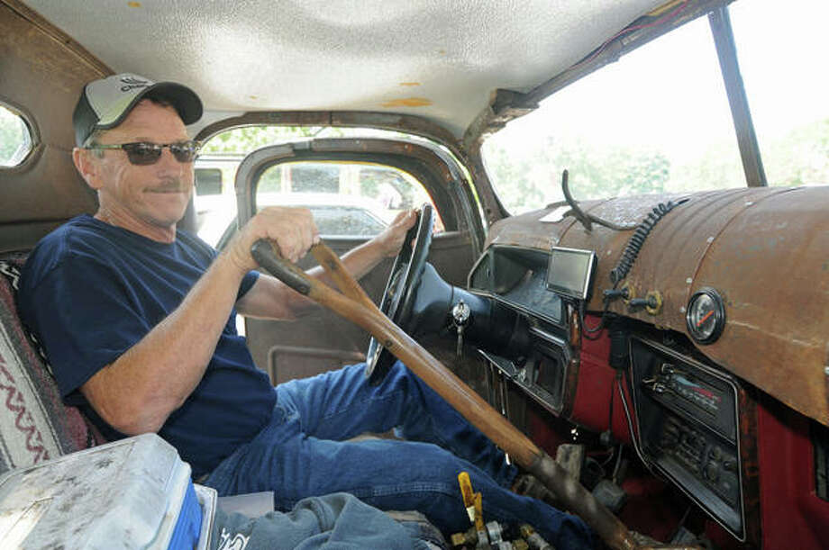 "Mark Releford of Hettick sits inside his home-built ""rat rod,"" complete with a shovel handle as a shifter. He shared his home-built vehicle Saturday at the Second Annual Car Show at Alton's Gordon Moore Park to benefit Foxes Grove Supportive Living in Wood River."