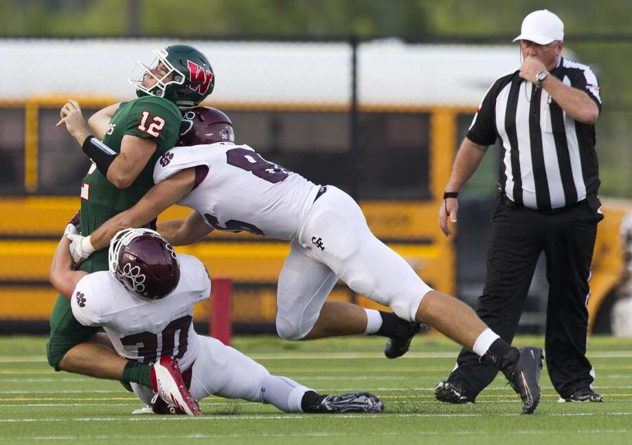 The Woodlands quarterback Ben Mills (12) is dragged down by Cy-Fair linebacker Hunter Warren (30) and defensive end Jack McCarty (86) during the first quarter of a non-district high school football game at Woodforest Bank Stadium, Saturday, Aug. 31, 2019, in Shenandoah. Photo: Jason Fochtman/Staff Photographer