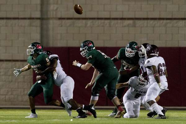 The Woodlands running back Bryeton Gilford (5) fumbles the ball during the fourth quarter of a non-district high school football game at Woodforest Bank Stadium, Saturday, Aug. 31, 2019, in Shenandoah. Cy-Fair recovered the ball for the Bobcats.