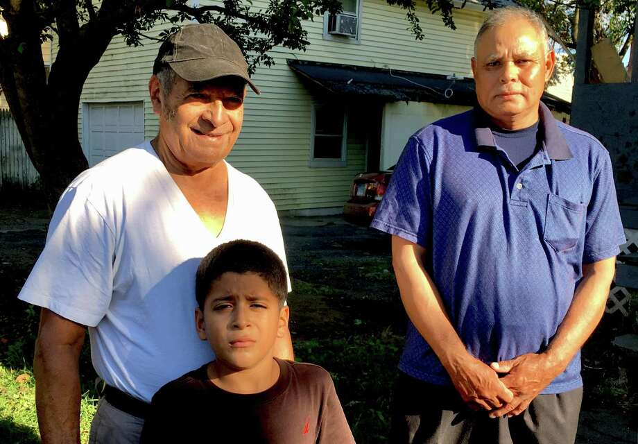 Fausto Canelas, left, from Honduras, with his grandson Emmanuel, 7, and Juan Mejia, from El Salvador. The two men live in Bridgeport under the Temporary Protected Status program and work as building cleaners in Norwalk with 32BJ SEIU. Photo: Dan Haar / Hearst Connecticut Media