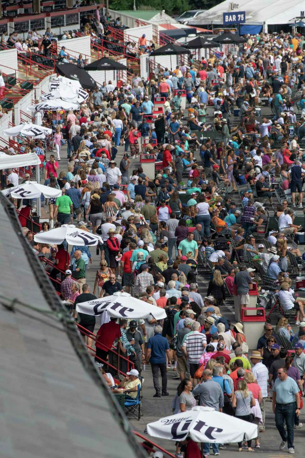 A huge line forms near the umbrellas at the Saratoga Race Course on sweatshirt giveaway day Sunday Sept. 1, 2019 in Saratoga Springs, N.Y. Photo Special to the Times Union by Skip Dickstein