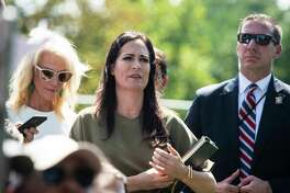 White House press secretary Stephanie Grisham listens as President Donald Trump stops to talk to reporters and members of the media at the White House on Aug. 21, 2019.