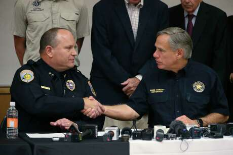 Texas Gov. Greg Abbott right, shakes hands with Odessa Police Department Chief Michael Gerke during a press conference at the University of Texas of the Permian Basin, Sunday, Sept. 1, 2019. Seth Aaron Ator, 36, of Odessa, is suspected of killing seven people an injuring 19 in a shooting spree on Saturday.