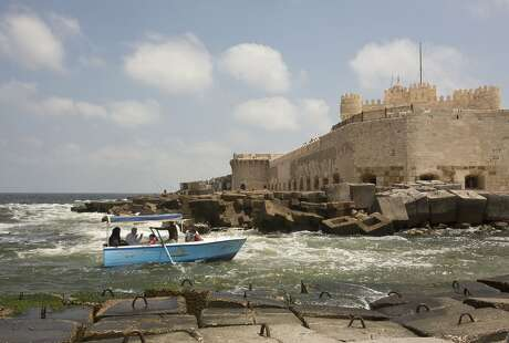 In this Aug. 8, 2019, photo, a family takes a ride in a boat moving between cement blocks placed as reinforcement against rising water levels near the citadel in Alexandria, Egypt. Alexandria, which has survived invasions, fires and earthquakes since it was founded by Alexander the Great more than 2,000 years ago, now faces a new menace from climate change. Rising sea levels threaten to inundate poorer neighborhoods and archaeological sites, prompting authorities to erect concrete barriers out at sea to hold back the surging waves. (AP Photo/Maya Alleruzzo)