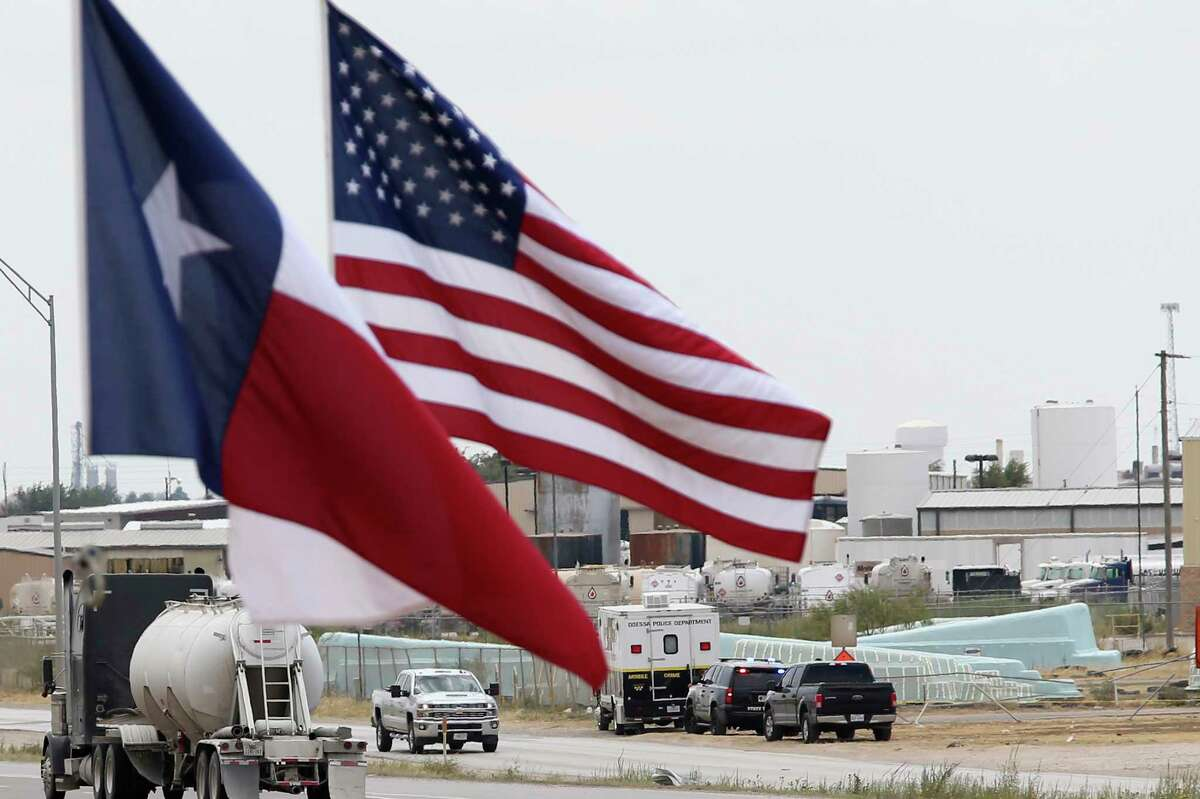 Law enforcement vehicles are seen behind the U.S. and Texas flags hanging from tow trucks along IH-20 near the Odessa, Texas city limits, Sunday, Sept. 1, 2019. Seth Aaron Ator, 36, of Odessa, is suspected of killing seven people an injuring 19 in a shooting spree in Odessa on Saturday. Before the rampage, Ator was stop along IH-10 between Odessa and Midland by a Texas Department of Public Safety trooper for a traffic violation.