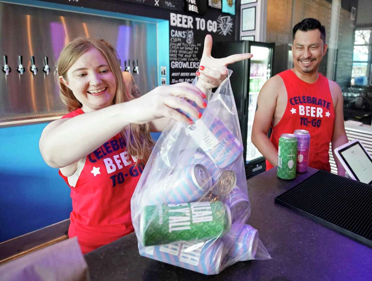 Julie Peters, left, and Jorge Benitez, right, prepare a beer to go order for customer Joel Swift at Holler Brewing Co., 2206 Edwards St., Sunday, Sept. 1, 2019, in Houston. Swift was the first person in line to buy beer to go on the first day of a new law that allows take-home sales from manufacturing breweries. Texas became the final state in the country to legalize take-home sales from manufacturing breweries as the result of a law passed during the 2019 Texas legislative session. With the new law, beer can be sold at 10 a.m. instead of noon on Sundays.