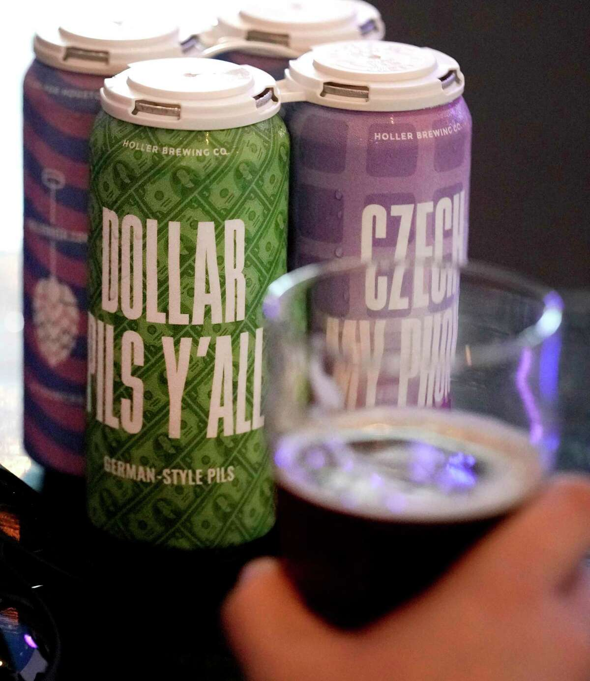 Cans of beer purchased to go sit on the table as customer Evan Camp of Houston drinks a beer at Holler Brewing Co., 2206 Edwards St., Sunday, Sept. 1, 2019, in Houston. Texas became the final state in the country to legalize take-home sales from manufacturing breweries as the result of a law passed during the 2019 Texas legislative session. With the new law, beer can be sold at 10 a.m. instead of noon on Sundays.
