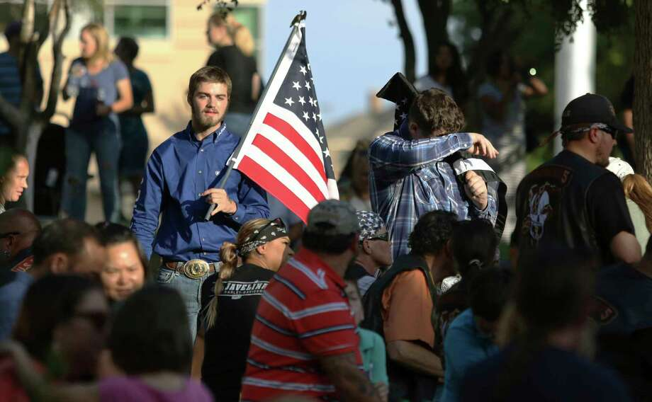 Travis Franklin and Holden Ewing carry American flags through the crowd gathered at the University of Texas Permian Basin in Odessa, Texas, Sunday, Sept. 1, 2019, to show their support for first responders and victims injured in Saturday's shooting. (Ben Powell/Odessa American via AP) Photo: Ben Powell, Associated Press / (C) The Odessa American
