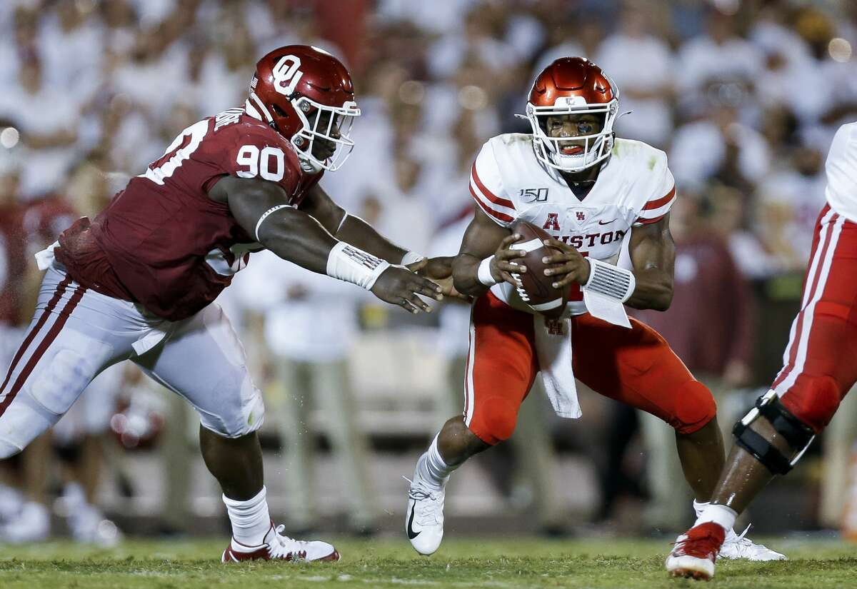 Houston Cougars quarterback D'Eriq King (4) avoids the pressure by Oklahoma Sooners defensive lineman Neville Gallimore (90) during the fourth quarter of an NCAA game at Gaylord Memorial Stadium Sunday, Sept. 1, 2019, in Norman, Oklahoma. The Sooners won 49-31.